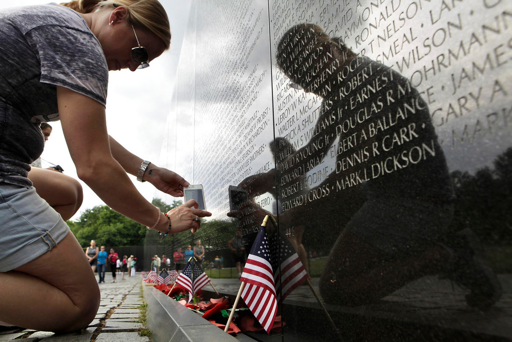 . A woman takes pictures of the Vietnam Veterans Memorial wall, etched with the names of more than 58,000 U.S. servicemen and women who died in the war, in Washington May 23, 2013. Memorial Day falls on May 27 this year.   REUTERS/Yuri Gripas
