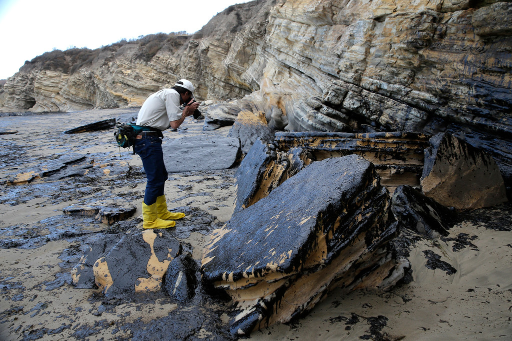 . David Ledig, a national monument manager from the Bureau of Land Management, takes pictures of rocks covered in oil at Refugio State Beach, north of Goleta, Calif., Thursday, May 21, 2015. More than 7,700 gallons of oil has been raked, skimmed and vacuumed from a spill that stretched across 9 miles of California coast, just a fraction of the sticky, stinking goo that escaped from a broken pipeline, officials said. (AP Photo/Jae C. Hong)