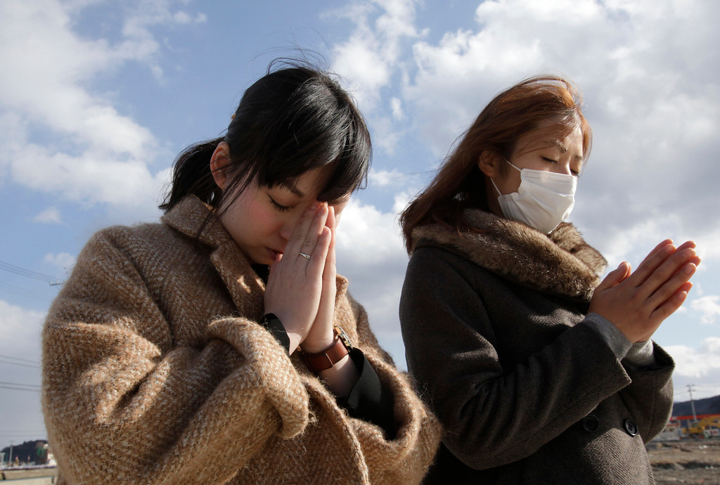 . People offer prayer in a moment of silence in front of what is left of a disaster control center in an area devastated by the March 11, 2011 earthquake and tsunami in Minamisanriku, Miyagi Prefecture, Monday, March 11, 2013. Japan marked the second anniversary on Monday of the devastating disasters that left nearly 19,000 people dead or missing. (AP Photo/Shizuo Kambayashi)