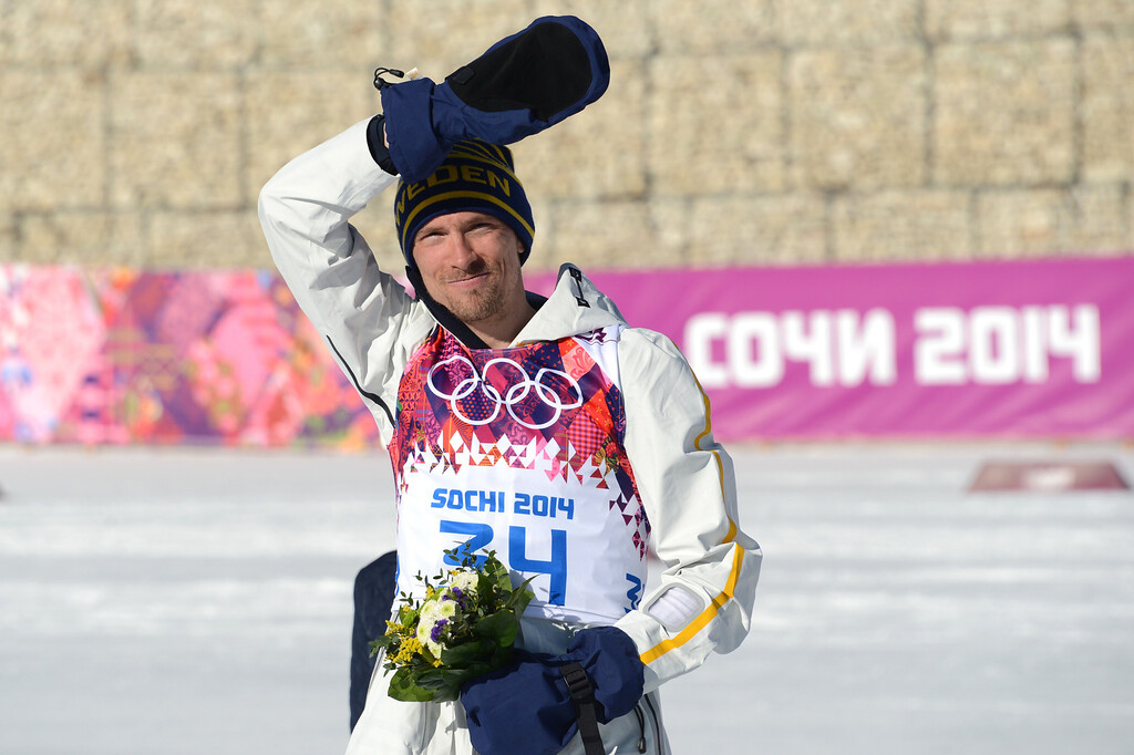 . Silver medalist Sweden\'s Johan Olsson celebrates on the podium in the Men\'s Cross-Country Skiing 15km Classic Flower Ceremony at the Laura Cross-Country Ski and Biathlon Center during the Sochi Winter Olympics on February 14, 2014 in Rosa Khutor near Sochi. AFP PHOTO / KIRILL KUDRYAVTSEV/AFP/Getty Images