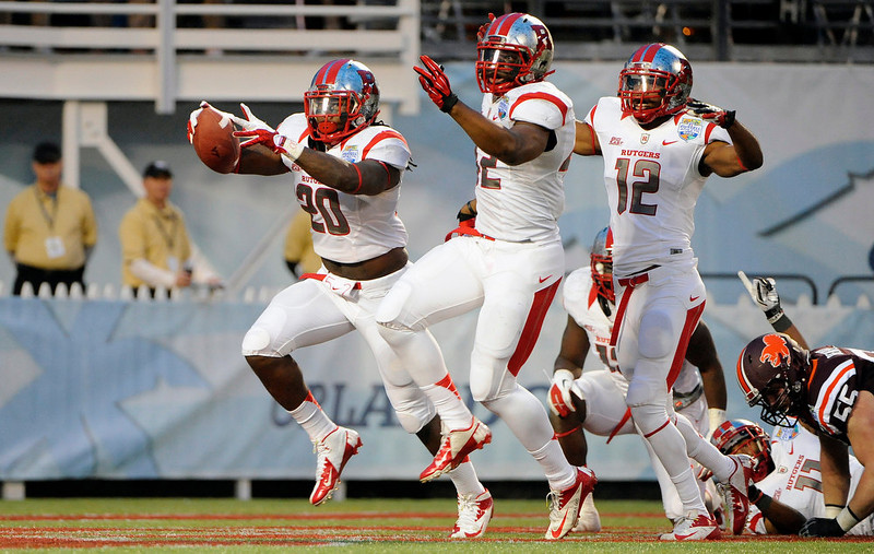 . Rutgers linebacker Khaseem Greene, left, celebrates with linebacker Steve Beauharnais, center, and defensive back Marcus Cooper (12) after recovering a fumble in the end zone for a touchdown during the first quarter of the NCAA college football Russell Athletic Bowl game against Virginia Tech, Friday, Dec. 28, 2012, in Orlando, Fla. (AP Photo/Brian Blanco)