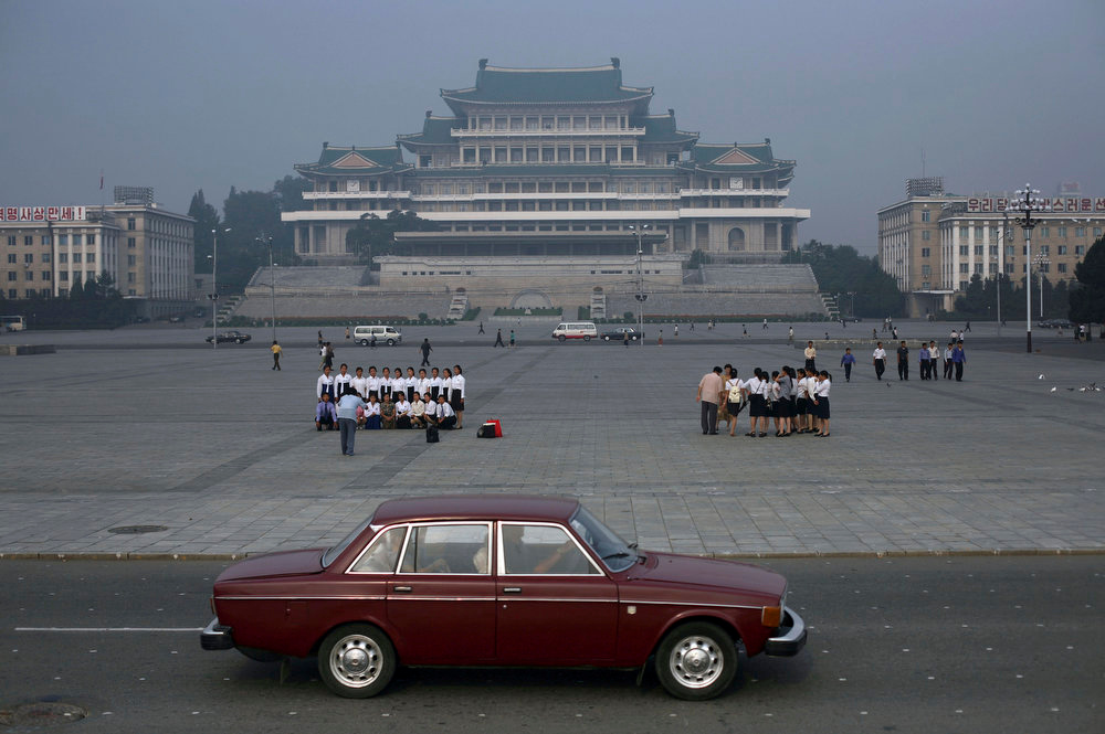 Description of . A car passes by as students tour Kim Il Sung Square in Pyongyang, North Korea on Wednesday, Sept. 17, 2008. (AP Photo/David Guttenfelder)