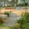 curved raised timber pathway with round posts and sandstone block retaining wall and spinners and timber seating steps and open cubby and dual blue plastic slide on mound