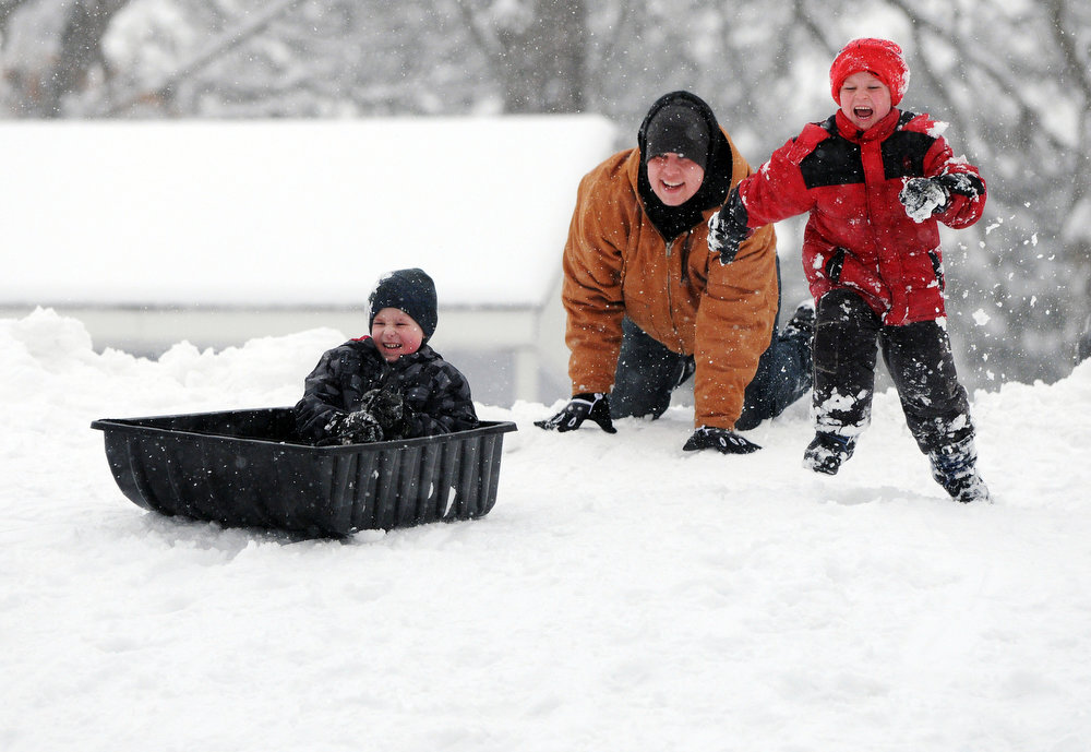 Description of . Xavier Maroff, left, gets a push from his dad Kyle as his brother Kayden races him down the sledding hill in the snow at Schadt Park in Silvis, Ill., on Tuesday, March 5, 2013. (AP Photo/The Dispatch, Todd Mizener)