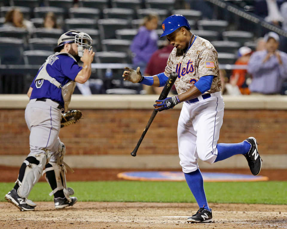 . New York Mets Curtis Granderson reacts after striking out in the sixth inning of a baseball game against the Colorado Rockies in New York, Monday, Sept. 8, 2014. Colorado Rockies catcher Michael McKenry (8) heads to the dugout after the strikeout. (AP Photo/Kathy Willens)