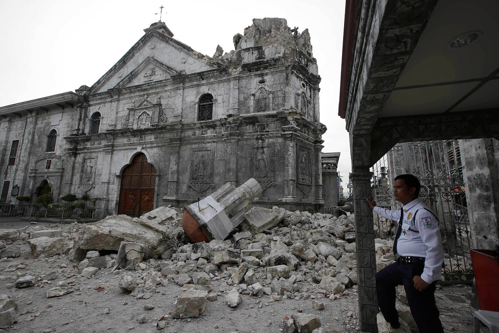 . A private guard stands near the damaged Basilica of the Holy Child following a 7.2-magnitude earthquake that hit Cebu city in central Philippines and toppled the bell tower of the Philippines\' oldest church Tuesday, Oct. 15, 2013.  (AP Photo/Bullit Marquez)