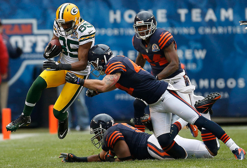 . Green Bay Packers\' Greg Jennings (L) runs upfield as Chicago Bears\' Chris Conte (C), Lance Briggs (bottom) and  Kelvin Hayden chase after him during the first half of their NFL football game at Soldier Field in Chicago December 16, 2012.     REUTERS/Jim Young