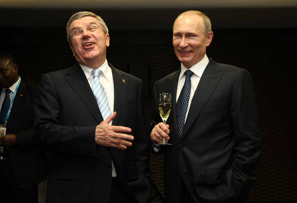 . (L-R) Thomas Bach the President of the International Olympic Committee and Vladimir Putin the President of Russia share a joke the Opening Ceremony of the Sochi 2014 Paralympic Winter Games at Fisht Olympic Stadium on March 7, 2014 in Sochi, Russia.  (Photo by Ian Walton/Getty Images)