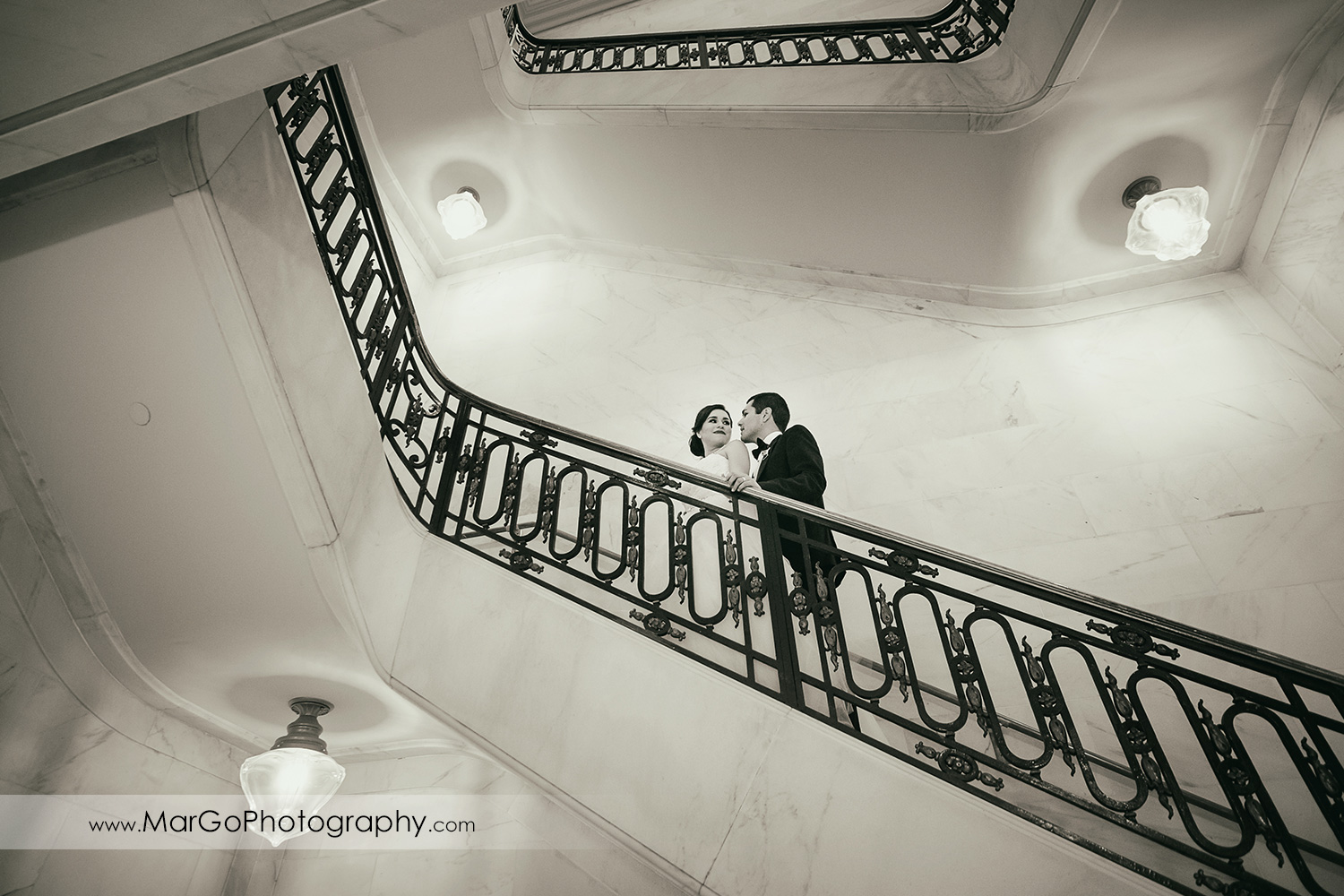 b&w bride and groom on the stairs in San Francisco City Hall