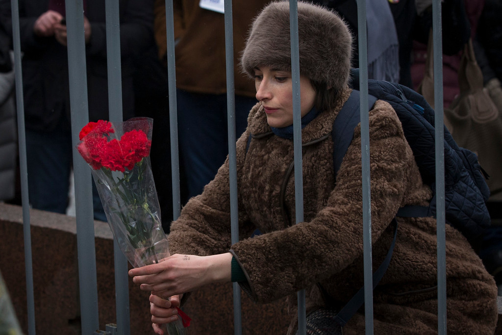 . A woman lays flowers at the place where Boris Nemtsov, a charismatic Russian opposition leader and sharp critic of President Vladimir Putin, was gunned down on Friday, Feb. 27, 2015 near the Kremlin, in Moscow, Russia, Sunday, March 1, 2015. Thousands converged Sunday in central Moscow to mourn veteran liberal politician Boris Nemtsov, whose killing on the streets of the capital has shaken Russiaís beleaguered opposition. They carried flowers, portraits and white signs that said ìI am not afraid.î  (AP Photo/Pavel Golovkin)