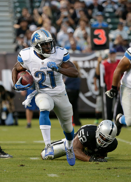 . Detroit Lions running back Reggie Bush (21) runs past Oakland Raiders outside linebacker Khalil Mack (52) during the first half of an NFL preseason football game in Oakland, Calif., Friday, Aug. 15, 2014. (AP Photo/Marcio Jose Sanchez)