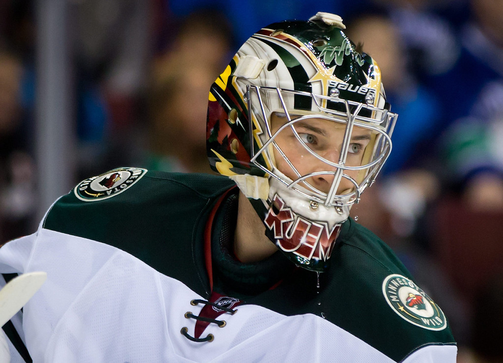 . Minnesota Wild goalie Darcy Kuemper pauses during a stoppage in the first period of an NHL hockey game against the Vancouver Canucks, Friday, Feb. 28, 2014, in Vancouver, British Columbia. (AP Photo/The Canadian Press, Darryl Dyck)