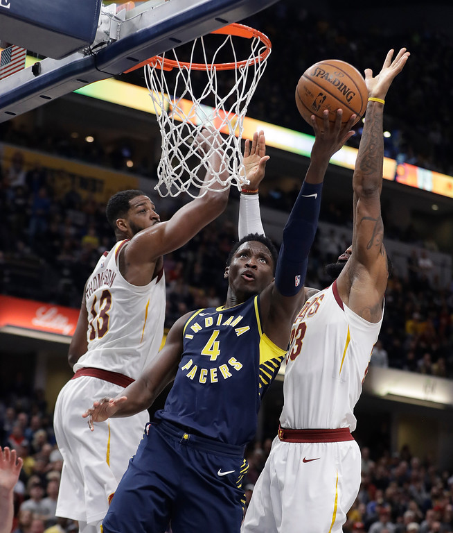. Indiana Pacers\' Victor Oladipo (4) shoots against Cleveland Cavaliers\' Tristan Thompson (13) and LeBron James during the second half of an NBA basketball game, Friday, Jan. 12, 2018, in Indianapolis. (AP Photo/Darron Cummings)