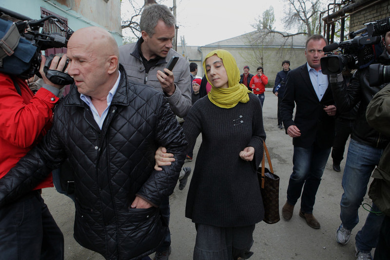 . Zubeidat Tsarnaeva, mother of Tamerlan and Dzhokhar Tsarnaev, the two men accused of setting off bombs near the Boston Marathon finish line on April 15, 2013 in Boston, is besieged by reporters as she walks with an unidentified man near her home in Makhachkala, Dagestan, southern Russia, Tuesday, April 23, 2013. The Tsarnaev brothers are accused of setting off the two bombs at the Boston Marathon on April 15 that killed three people and wounded more than 200. Tsarnaev, 26, was killed in a gun battle with police. His 19-year-old brother, Dzhokhar Tsarnaev, was later captured alive, but badly wounded.  (AP Photo/Ilkham Katsuyev)