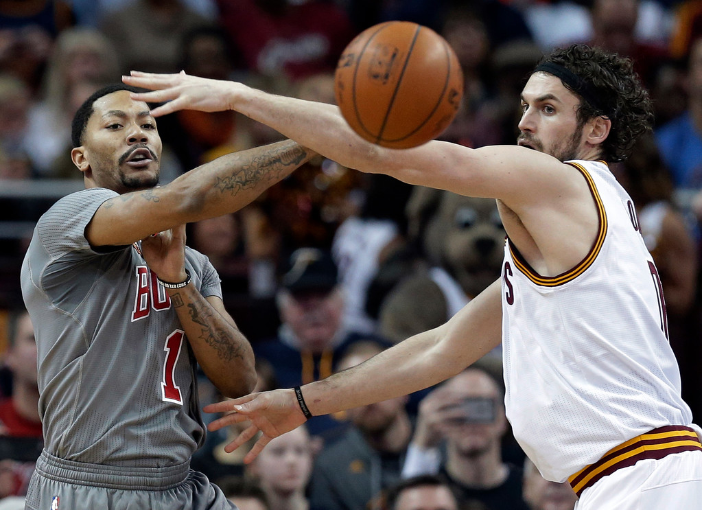 . Chicago Bulls\' Derrick Rose (1) passes over Cleveland Cavaliers\' Kevin Love (0) in the first half of an NBA basketball game Saturday, Jan. 23, 2016, in Cleveland. (AP Photo/Tony Dejak)