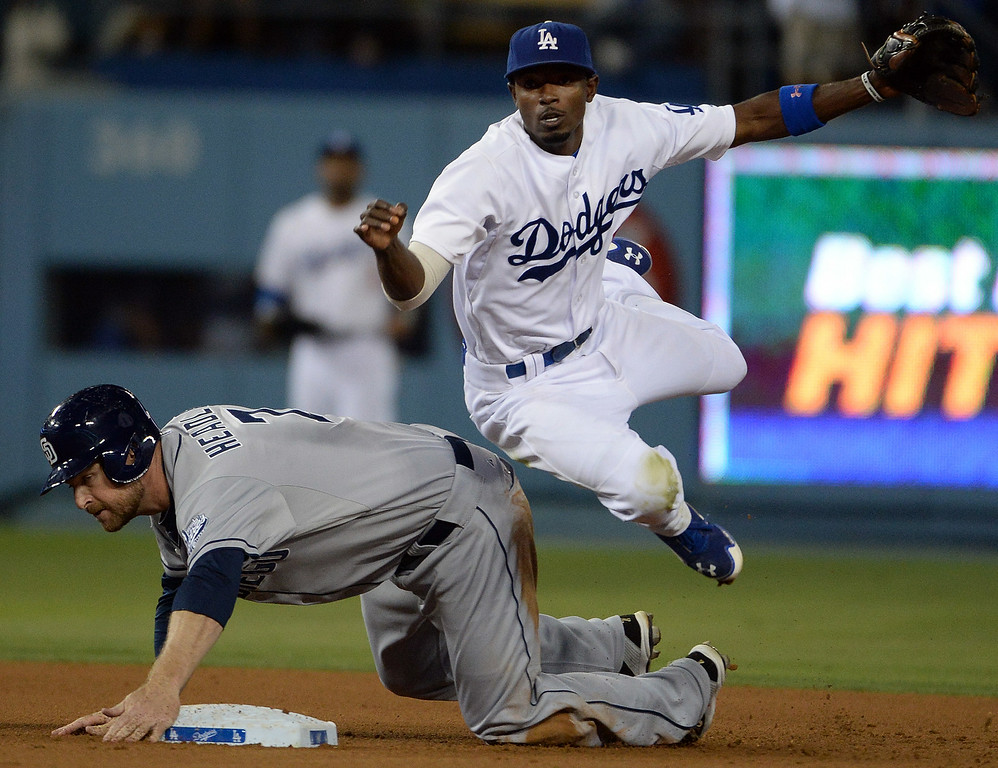 . Los Angeles Dodgers second baseman Dee Gordon forces out San Diego Padres\' Chase Headley (7) at second base as he throws to first to complete the double play on Carlos Quentin (not pictured) in the seventh inning of a Major league baseball game on Saturday, July 12, 2014 in Los Angeles.   (Keith Birmingham/Pasadena Star-News)
