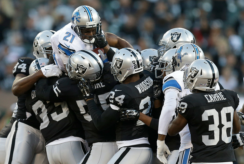 . Detroit Lions running back Reggie Bush (21) is tackled by Oakland Raiders defenders during the first half of an NFL preseason football game in Oakland, Calif., Friday, Aug. 15, 2014. (AP Photo/Ben Margot)