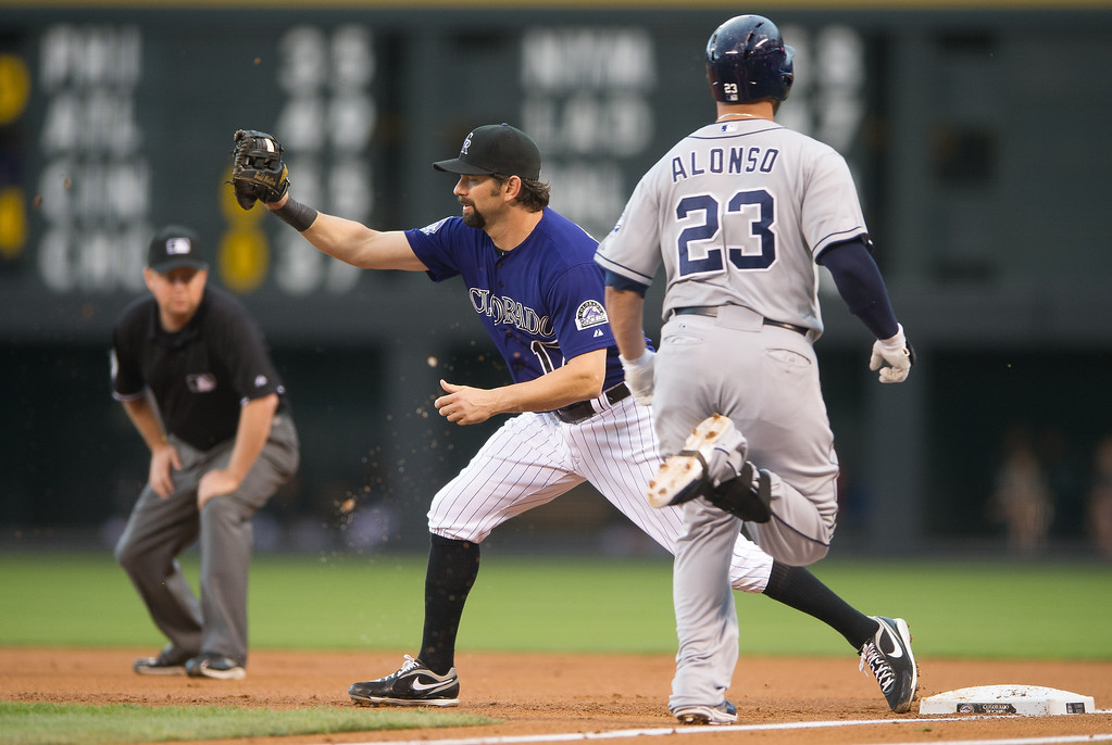 . Todd Helton #17 of the Colorado Rockies puts out Yonder Alonso #23 of the San Diego Padres at first base in the first inning of a game at Coors Field on August 12, 2013 in Denver, Colorado. The Rockies led the Padres 2-0 after one inning.  (Photo by Dustin Bradford/Getty Images)