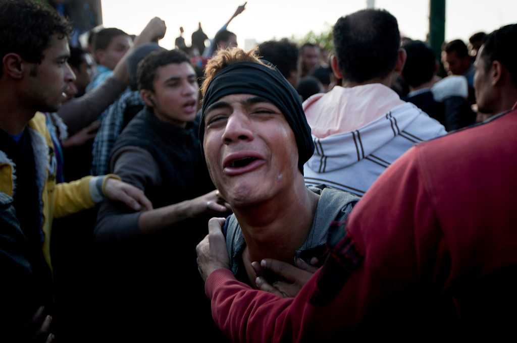 . A protester mourns his fatally wounded comrade, unseen, after evacuating him from the scene of clashes in downtown Cairo, Egypt, Saturday, March 9, 2013.  (AP Photo/Nasser Nasser)