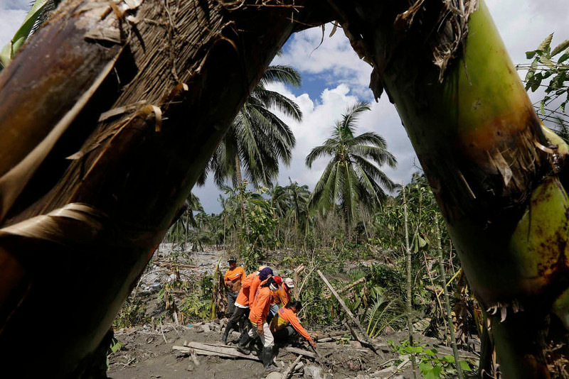 . Rescuers prepare to dig up another flash flood victim at the village of Andap, New Bataan township, Compostela Valley in southern Philippines Saturday, Dec. 8, 2012. Search and rescue operations following a typhoon that killed nearly 600 people in the southern Philippines have been hampered in part because many residents of this ravaged farming community are too stunned to assist recovery efforts, an official said Saturday.  (AP Photo/Bullit Marquez)
