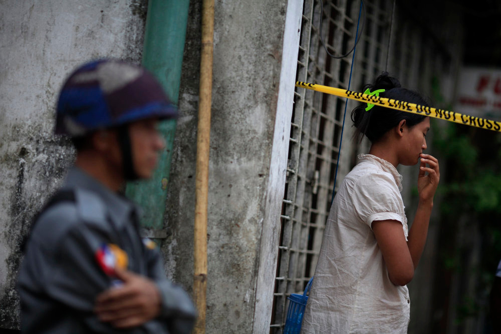 . A woman stands behind a police line near a mosque and school dormitory that were damaged by a fire in Yangon April 2, 2013. An electrical fire at an Islamic school in Myanmar\'s biggest city killed 13 children early on Tuesday, authorities said. The children, all boys, died of suffocation in the fire at the dormitory of a school next to the mosque in Yangon at about 2:40 a.m., neighbors and officials said. REUTERS/Soe Zeya Tun
