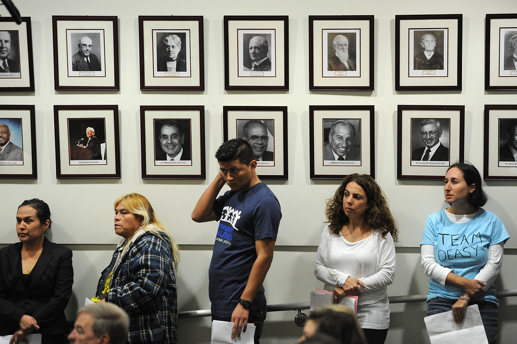 . People waiting to speak in support of LAUSD Superintendent John Deasy stand under pictures of previous superintendents at a board meeting at LAUSD headquarters, Tuesday, October 29, 2013. (Photo by Michael Owen Baker/L.A. Daily News)
