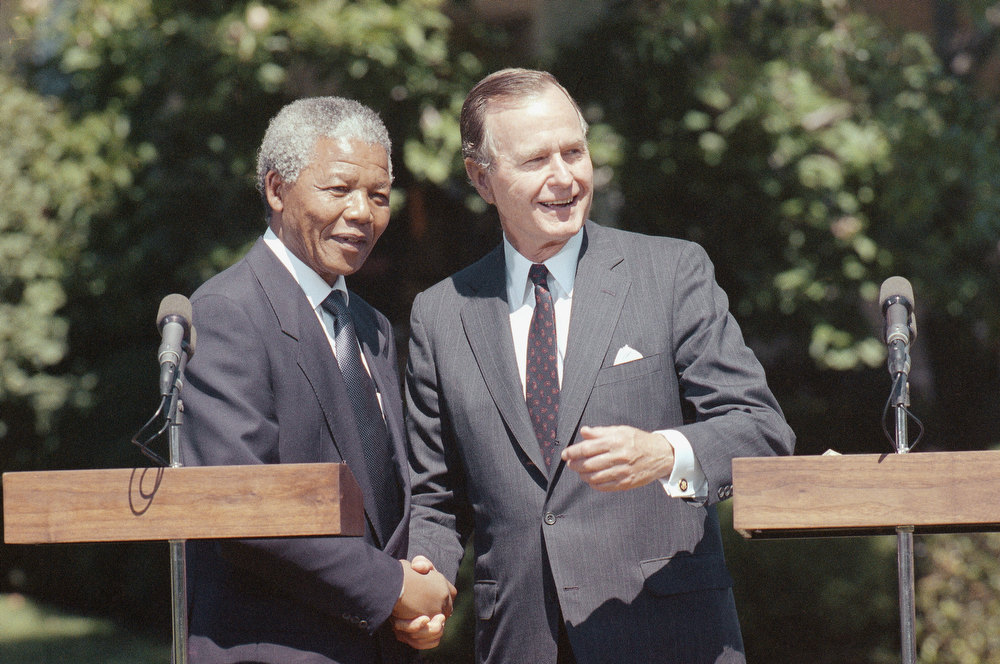 Description of . In this June 25, 1990 file photo, President George H W  Bush greets African National Congress Deputy President Nelson Mandela at the White House  in Washington.  (AP Photo/Doug Mills, file)
