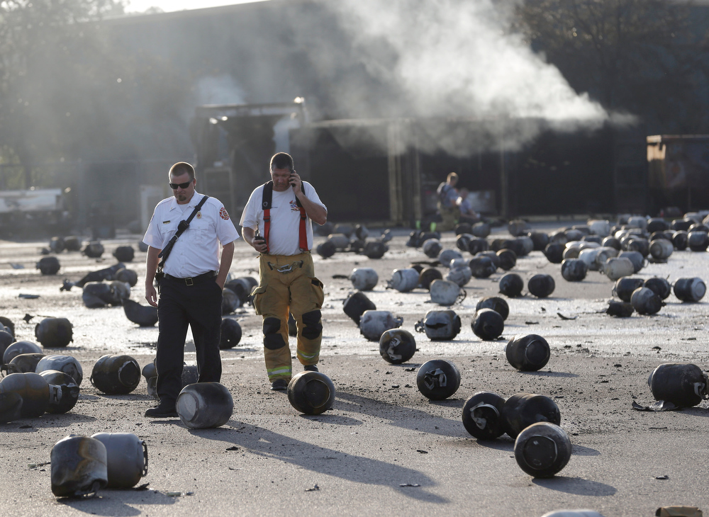 . Firefighters walk through an area of exploded propane cylinders in the aftermath of an explosion and fire at a propane gas company, Tuesday, July 30, 2013, in Tavares, Fla. Eight people were injured, with at least three in critical condition. John Herrell of the Lake County Sheriff\'s Office said early Tuesday there were no fatalities despite massive blasts that ripped through the Blue Rhino propane plant late Monday night. (AP Photo/John Raoux)