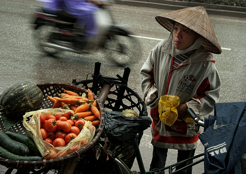 This farmer cycles from the countryside into Saigon. She then braves the anarchy on the roads and the weather and makes a living selling her produce.   Saigon, Vietnam, 2008