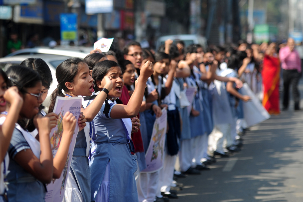 Description of . Bangladeshi school girls form a human chain as they participate in a One Billion Rising rally in Dhaka on February 14, 2013. The one-day event called for one billion women around the world to walk away from their homes, businesses, and jobs, and join together to dance in a show of collective strength. The word