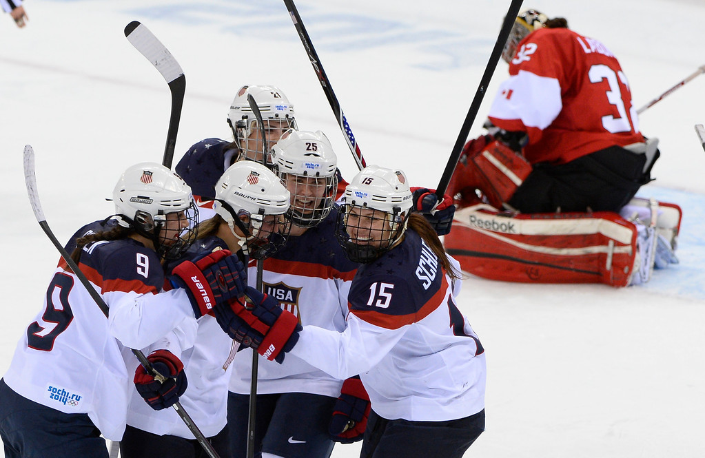 . US Hilary Knight (3rd L) celebrates with team mates after scoring a goal during the Women\'s Ice Hockey Group A match between Canada and USA at the Sochi Winter Olympics on February 12, 2014 at the Shayba Arena. AFP PHOTO / JONATHAN NACKSTRAND/AFP/Getty Images
