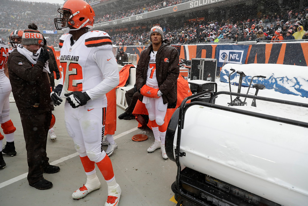 . Cleveland Browns offensive tackle Shon Coleman (72) and quarterback DeShone Kizer (7) try and stay warm near heaters during an NFL football game against the Chicago Bears in Chicago, Sunday, Dec. 24, 2017. (AP Photo/Charles Rex Arbogast)