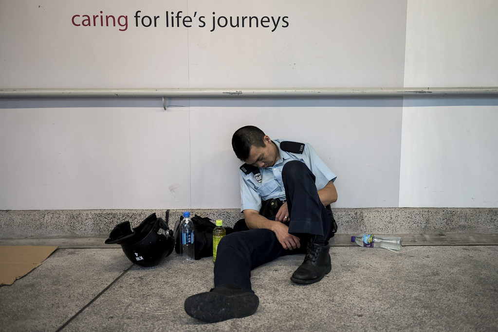 . A police officer rests as a pro-democracy rally continues near the government headquarters in Hong Kong on September 28, 2014.  Activists massed outside Hong Kong\'s government headquarters on September 28, vowing to keep up an increasingly tense civil disobedience campaign unless Beijing grants more political freedoms.  AFP PHOTO / ALEX OGLEAlex Ogle/AFP/Getty Images