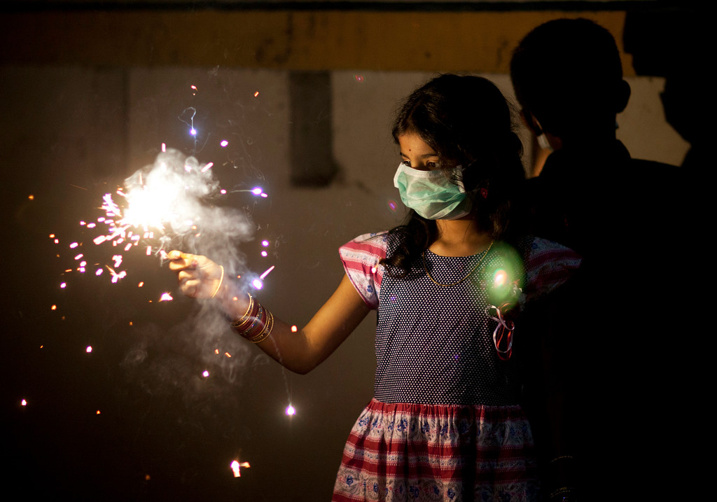 . An Indian girl wears a mask while playing with firecrackers to celebrate Diwali in Hyderabad, India, Thursday, Oct. 19, 2017. Hindus light lamps, wear new clothes, exchange sweets and gifts and pray to goddess Lakshmi during Diwali, the festival of lights. (AP Photo/Mahesh Kumar A.)