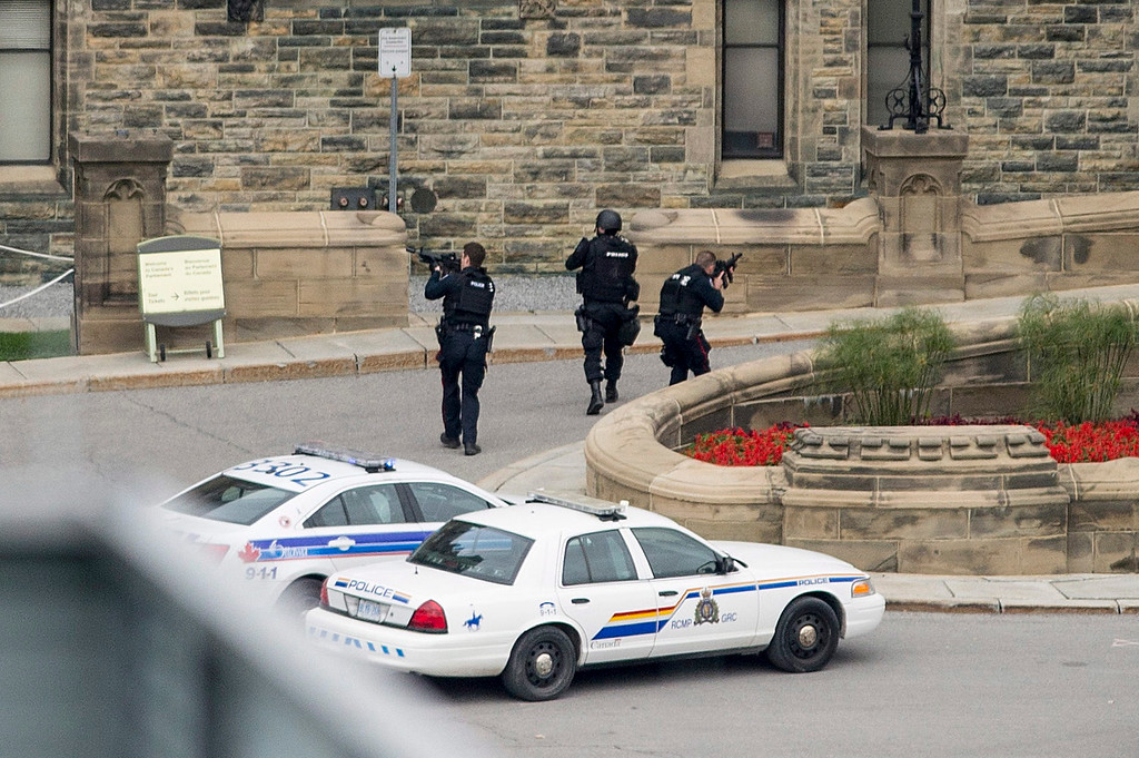. Police teams enter Centre Block at Parliament Hill in Ottawa on  Wednesday Oct. 22, 2014.  A soldier standing guard at the National War Memorial was shot by an unknown gunman and people reported hearing gunfire inside the halls of Parliament. Prime Minister Stephen Harper was rushed away from Parliament Hill to an undisclosed location, according to officials. (AP Photo/The Canadian Press, Justin Tang)