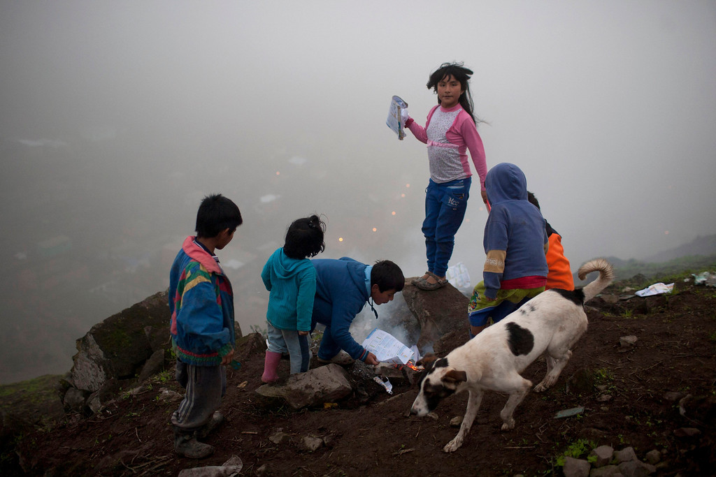 . In this Aug. 6, 2013 photo, children light a bonfire at the Virgen de las Mercedes neighborhood in Lima, Peru. For roughly four months a year, the sun abandons Peru\'s seaside desert capital, suffocating it under a ponderous gray cloudbank and fog that coats the city with nighttime drizzles. Of course no one suffers Lima\'s winters like the poor huddled in its hilly, fog-draped peripheries. (AP Photo/Rodrigo Abd)