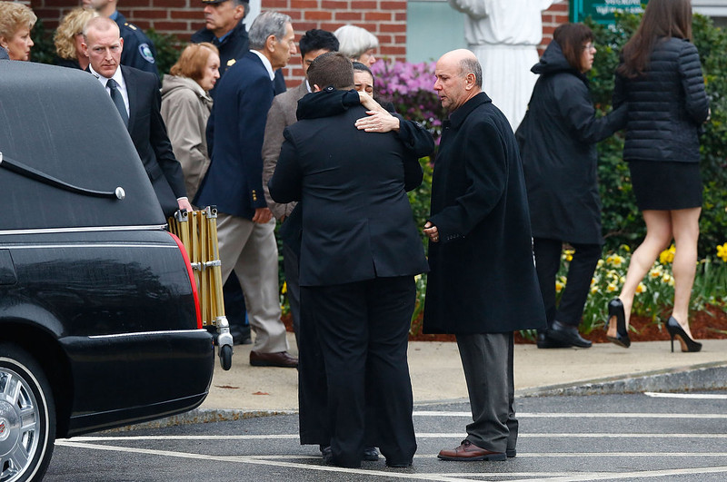 . Mourners embrace one another outside of St Patrick\'s Church following the funeral for the slain Massachusetts Institute of Technology (MIT) police officer Sean Collier on April 23, 2013 in Stoneham, Massachusetts. Collier was allegedly shot by the suspects in the Boston Marathon bombing, Dzhokhar A. Tsarnaev, 19, and his brother Tamerlan Tsarnaev, 26, after their identities were determined and a manhunt was launched.  Tamerlan Tsarnaev was subsequently shot and killed after a car chase and shootout with police and Dzhokhar Tsarnaev was apprehended on a boat parked on a residential property in Watertown, Massachusetts. The bombing, on April 15 at the finish line of the marathon, killed three people and wounded at least 170.  (Photo by Jared Wickerham/Getty Images)