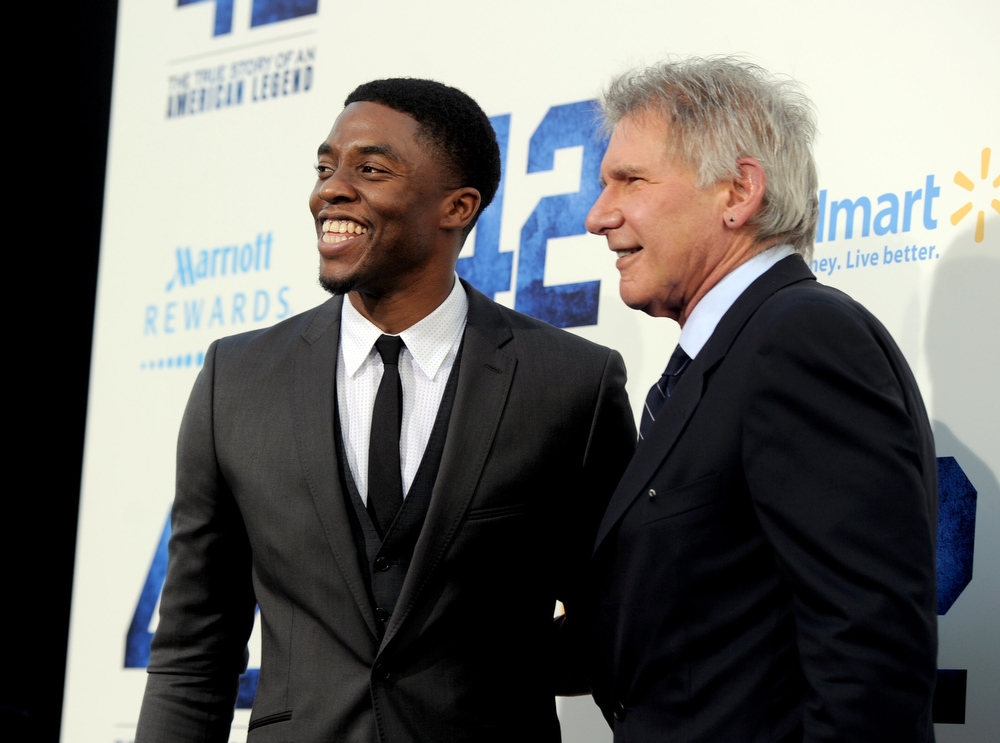 ". Actors Chadwick Boseman (L) and Harrison Ford arrive at the premiere of Warner Bros. Pictures\' and Legendary Pictures\' ""42\"" at the Chinese Theatre on April 9, 2013 in Los Angeles, California.  (Photo by Kevin Winter/Getty Images)"