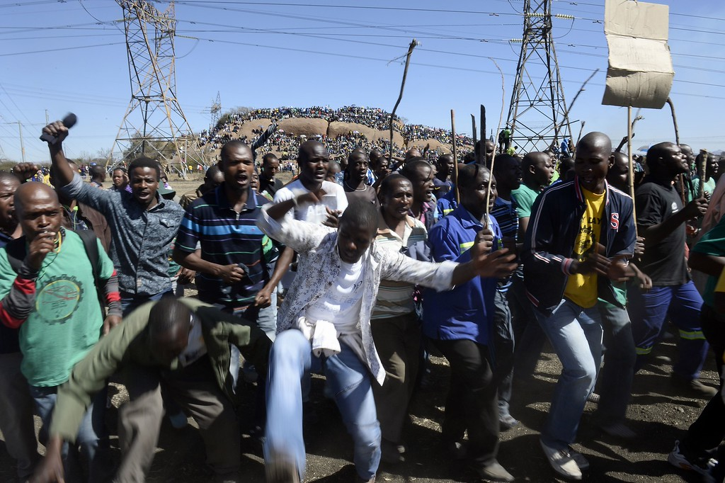 . Co-workers of 34 miners shot dead by South African police during a violent wage strike sing and dance on August 16, 2013 in Marikana to mark the first anniversary of their deaths. Today marks a year after police opened fire on thousands of strikers at platinum producer Lonmin\'s mine, northwest of Johannesburg, which killed 34 and injured 78 people. The August shooting was described as the worst police brutality since the end of apartheid two decades ago. Three days ago, the firm has recognised radical labour group AMCU, which led the wage strike, in an attempt to ease simmering inter-union tensions on the platinum belt. STEPHANE DE SAKUTIN/AFP/Getty Images