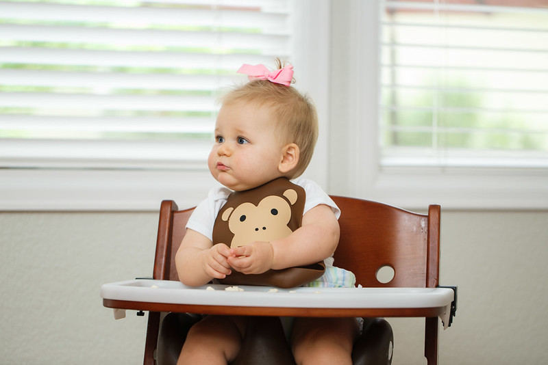 Make_My_Day_Bib_Lifestyle_Monkey_Girl_In_Highchair_Looking_Left_Playing_With_Food.JPG