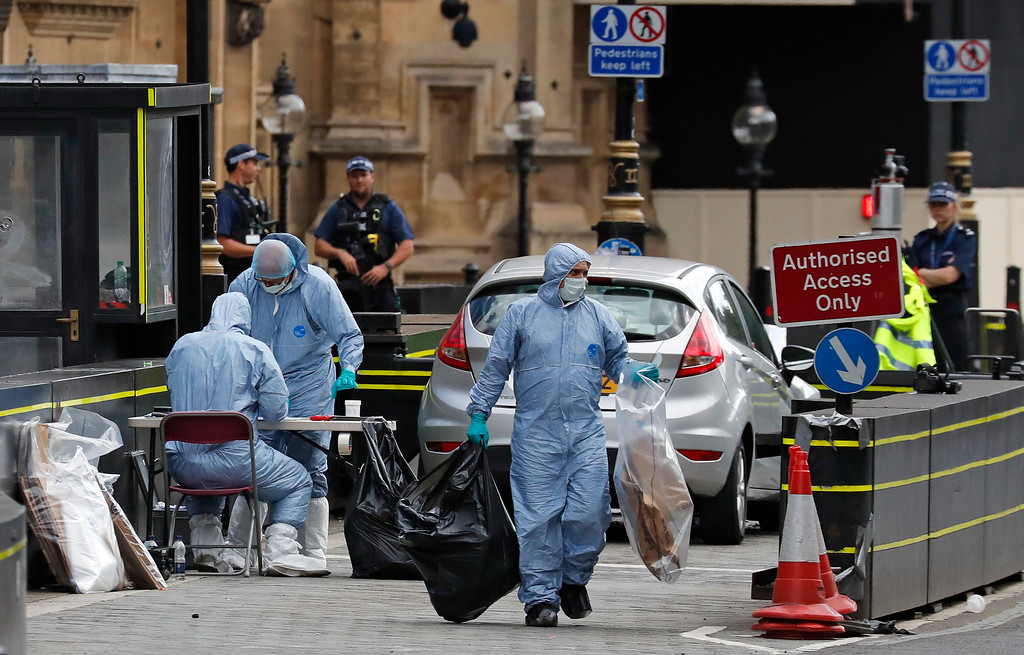 . Forensics officers carry away bags from the car that crashed into security barriers outside the Houses of Parliament in London, Tuesday, Aug. 14, 2018. Authorities said in a statement Tuesday that a man in his 20s was arrested on suspicion of terrorist offenses after a silver Ford Fiesta collided with a number of cyclists and pedestrians before crashing into the barriers during the morning rush hour. (AP Photo/Frank Augstein)
