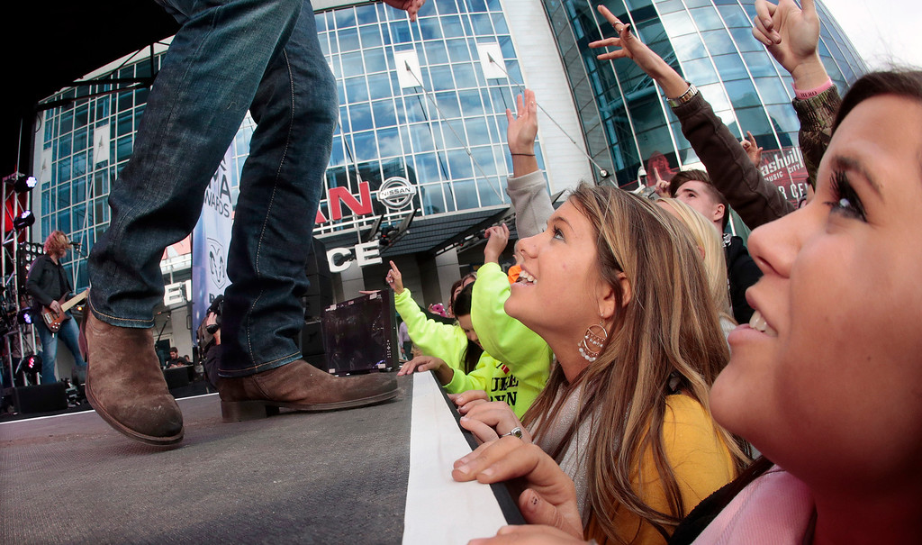. Fans watch as Luke Bryan performs outside of Bridgestone Arena on Wednesday, Nov. 6, 2013, in Nashville, Tenn. The Country Music Association Awards will be held at the venue Wednesday night. (AP Photo/Mark Humphrey)