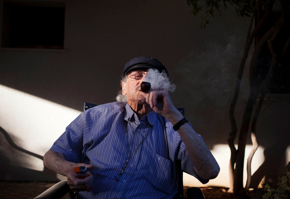 Description of . In this photograph made on Tuesday, Oct. 30, 2012, Moshe Rute, 80, smokes medical cannabis at the old age nursery home in kibbutz Naan next to the city of Rehovot, Israel. Marijuana is illegal in Israel but medical use has been permitted since the early nineties for cancer patients and those with pain-related illnesses such as Parkinson's, Multiple Sclerosis, and even post-traumatic stress disorder. (AP Photo/Dan Balilty)