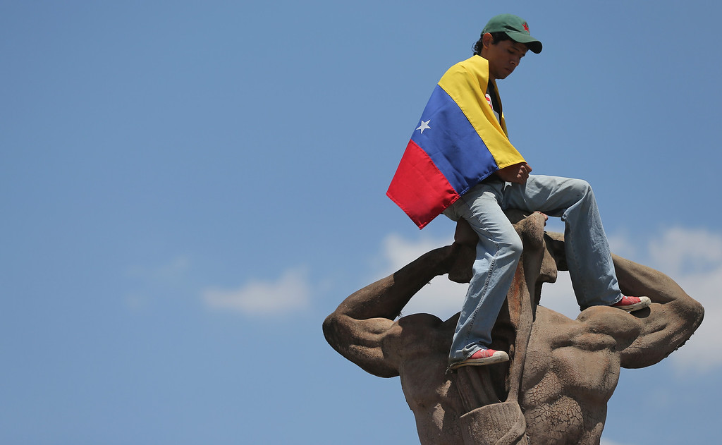 . A young man wears a Venezuelan flag atop a statue outside the funeral for Venezuelan President Hugo Chavez at the Military Academy on March 8, 2013 in Caracas, Venezuela..  (Photo by Mario Tama/Getty Images)