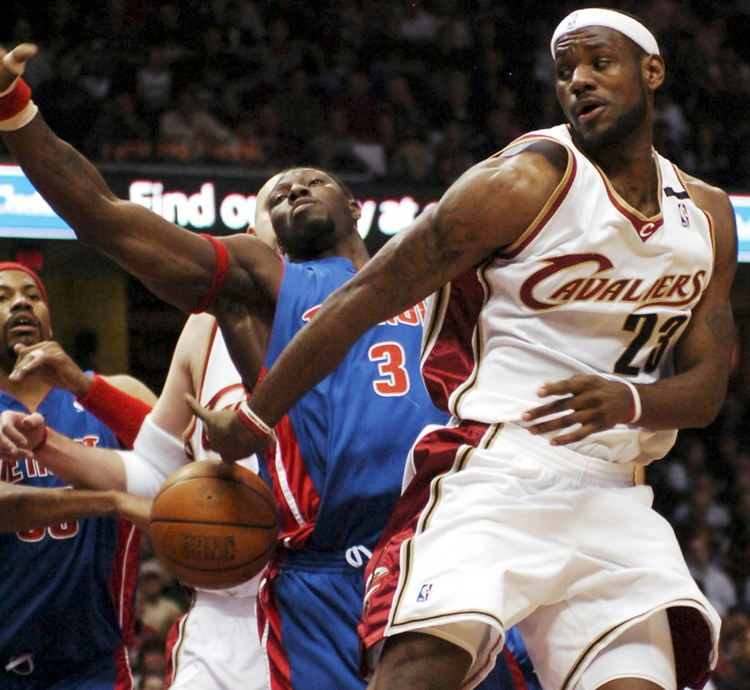 . MORNING JOURNAL/DAVID RICHARD LeBron James attempts a behind-the-back pass to teammate Zydrunas Ilgauskas last night against the Pistons. Defending for Detroit are Ben Wallace, #3, and Rasheed Wallace.