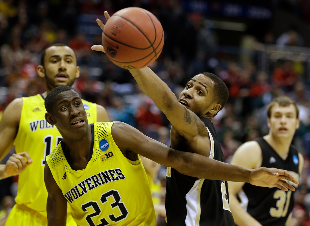 . Michigan guard Caris LeVert (23) and Wofford guard Jaylen Allen battle for a rebound during the first half of a second round NCAA college basketball tournament game Thursday, March 20, 2014, in Milwaukee. (AP Photo/Jeffrey Phelps)