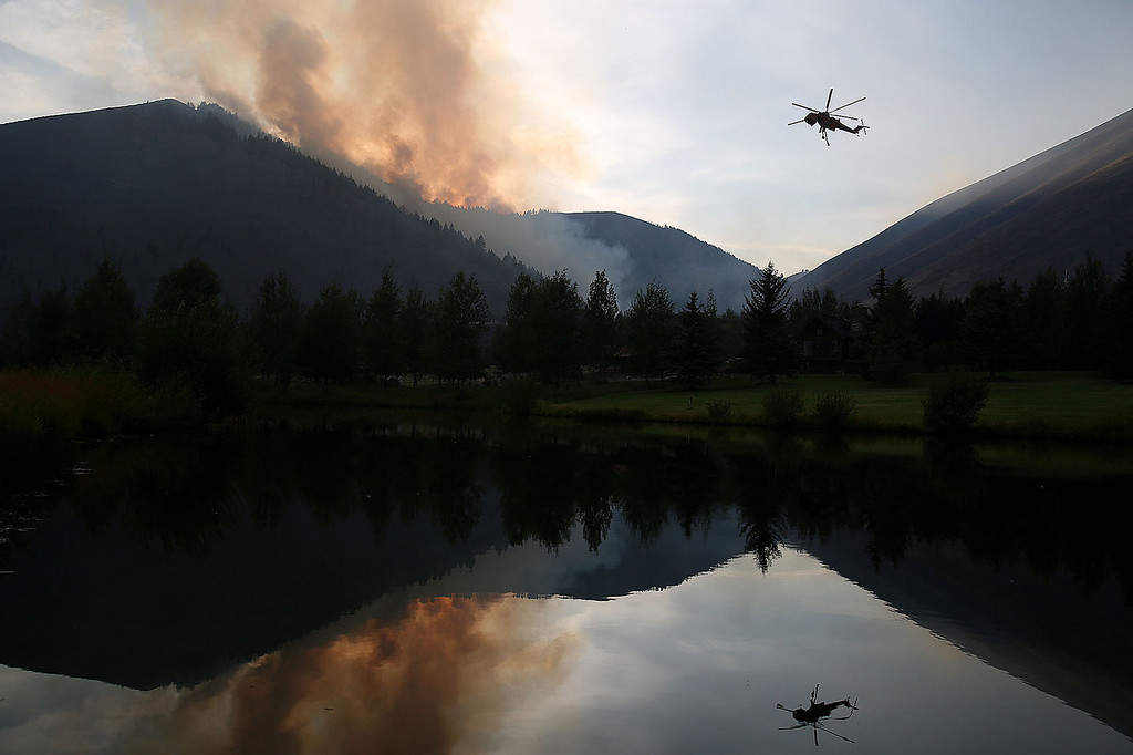 . A helicopter descends in the Golden Eagle Subdivision to refill with water from a pond while battling the Beaver Creek Fire on Saturday, Aug. 17, 2013 north of Hailey, Idaho.(AP Photo/Times-News, Ashley Smith)
