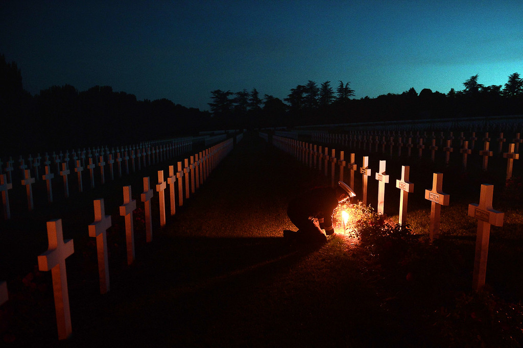 . Torchlights are placed next to soldiers\' tombs at the Douaumont\'s boneyard, eastern France, during the annual event known as The Four Days of Verdun, a night parade of veterans, as they commemorate the Verdun battle 98th anniversary. AFP PHOTO/FREDERICK  FLORIN/AFP/Getty Images