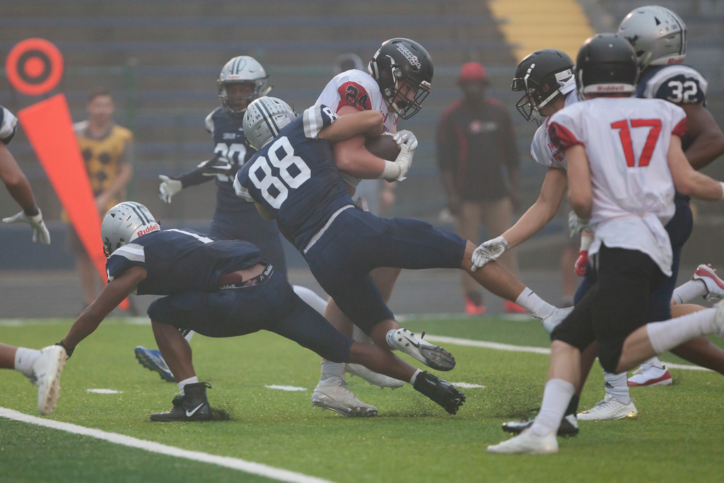 . Jen Forbus - The Morning Journal<br> Lorain linebacker Zach Evans wraps up St. Joseph fullback Aiden Arnott-Smith on Sept. 15.