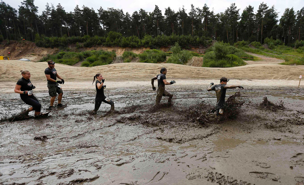 """. Participants of the \""""Tough Mudder\"""" endurance event series run through the \""""Mud Mile\"""" obstacle in the Fursten Forest, a former British Army training ground near the north-western German city of Osnabrueck July 13, 2013. The hardcore but un-timed event over 16 km (10 miles) was designed by British Special Forces to test mental as well as physical strength. Some 4,000 competitors had to overcome obstacles of common human fears, such as fire, water, and heights.   REUTERS/Wolfgang Rattay"""